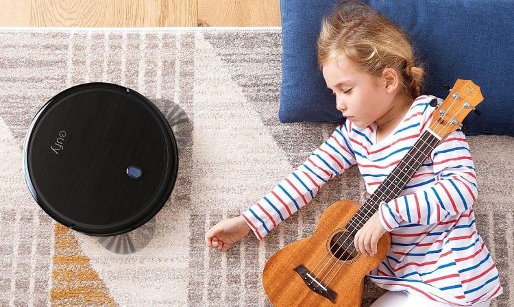 Girl Laying Next To Robot Vacuum