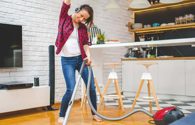 happy young girl vacuuming with headphones